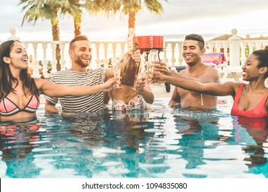 Happy friends cheering with champagne in pool party at sunset - Rich people having fun in exclusive tropical vacation outdoor- Holiday, youth lifestyle and friendship concept - Focus on men faces