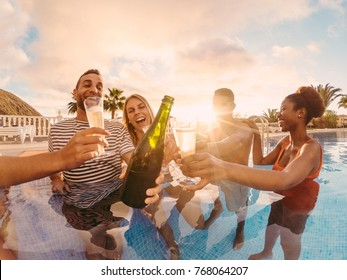 Happy friends cheering with champagne in pool party at sunset - Rich people having fun in exclusive tropical vacation - Holiday and friendship concept - Main focus on left man - Sun tones filter