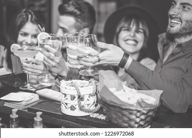 Happy friends cheering with cockatil in a vintage bar - Young people having fun toasting glasses of cocktails in a pub club - Friendship, holidays and youth lifestyle
