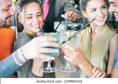 Happy friends cheering with cocktails in a bar outdoor - Young millennial people having fun drinking alcohol and laughing together - Youth lifestyle party concept