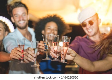 Happy friends cheering and drinking champagne at beach party outdoor - Young millennials people having fun at weekend summer night - Youth lifestyle and nightlife concept - Focus on hands glasses