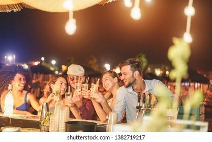 Fröhliche Freunde jubeln und trinken Cocktails bei Strandparty im Freien - Junge Jahrtausende Menschen, die am Wochenende Sommernacht Spaß haben - Jugendlifestyle und Nachtleben - Schwerpunkt auf Jungs