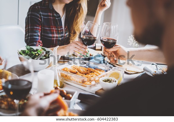 Happy friends cheering with glasses of red wine at restaurant with healthy food, group of people enjoying and toasting at home, togetherness and friendship concept, filtered image