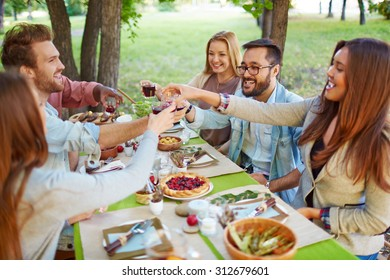 Happy friends cheering up at Thanksgiving party outdoors