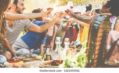 Happy friends cheering with wine glasses at picnic dinner outdoor - Young students having fun at bbq in winery vineyard - Food, summer lifestyle and youth concept - Focus on center glasses
