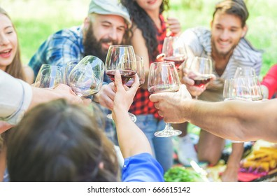 Happy friends cheering with wine glasses at picnic on city park outdoor - Young trendy people doing a toast and laughing together - Focus on bottom hands - Youth and friendship concept