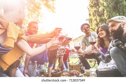 Happy friends cheering with wine glasses at pic-nic outdoor - Young students having fun doing a toast at sunset - Food, friendship and youth concept - Focus on left glasses - Warm filter