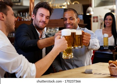 Happy friends clinking with beer mugs in pub, smiling.