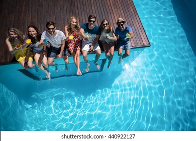 Happy friends with cocktail glass sitting side by side in swimming pool