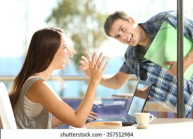 Happy friends or couple greeting waving hands and looking each other in a date in a coffee shop