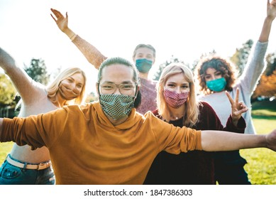 Happy friends covered by face masks having fun in the park - New normal concept with young people having party together outside. - Shutterstock ID 1847386303