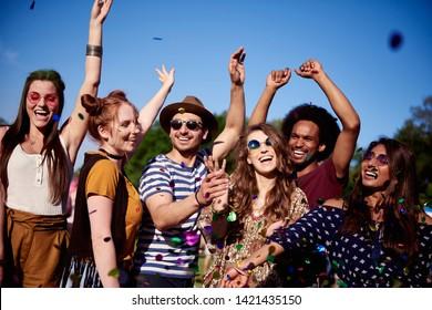 Happy friends dancing in confetti