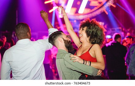 Happy friends dancing and drinking at party festival - Young people having fun celebrating new year's ev with cocktails in night club disco - Youth and nightlife concept - Soft focus on white man face