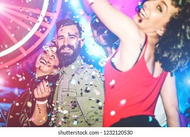 Happy friends dancing at night club festival with laser lights and confetti in background - Young millennials people having fun on party weekend nightlife - Youth concept - Focus on left man face