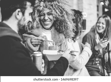 Happy friends from diverse culture eating street food outdoor - Yong trendy people having fun together drinking and laughing - City lifestyle and party concept - Focus on black girl face