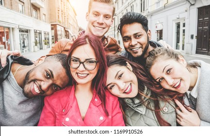Happy friends from diverse cultures and races taking selfie with back lighting - Youth, millennial generation and friendship concept with young people having fun together - Main focus on left two guys