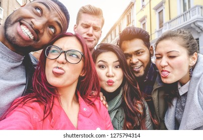 Happy friends from diverse cultures and races taking selfie making funny faces - Youth, millennial generation and friendship concept with young people having fun together - Main focus on left girl