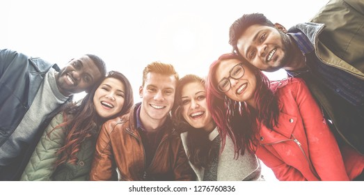 Happy friends from diverse cultures and races taking photo making funny faces - Youth, millennial generation and friendship concept with young people having fun together - Main focus on right guys