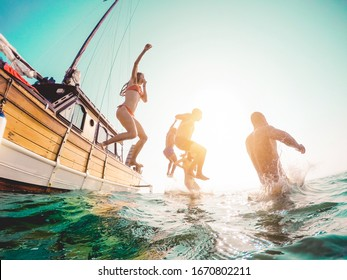 Happy friends diving from sailing boat into the sea - Young people jumping inside ocean in summer excursion day - Vacation, youth and fun concept - Main focus on close-up man - Fisheye lens distortion