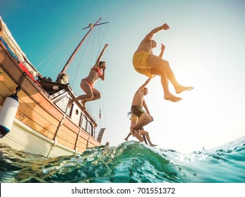Happy friends diving from sailing boat into the sea - Young people jumping inside ocean in summer excursion day - Vacation, youth and fun concept - Soft focus on left man - Fisheye lens distortion