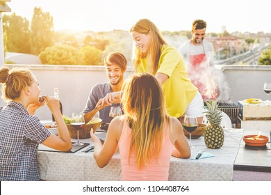 Happy friends doing barbecue dinner in patio terrace - Young millennial people having fun at bbq meal outdoor at summer sunset - Focus on girls hands - Youth lifestyle, friendship and party concept