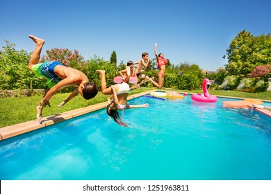 Happy friends doing front flip in swimming pool