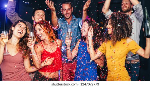 Happy friends doing party dancing and drinking champagne at nightclub - Millennial young people having fun celebrating together and throwing confetti - Entertainment, youth lifestyle holidays concept