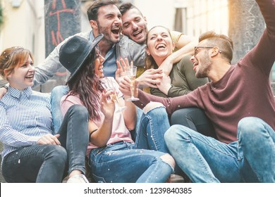 Happy friends doing party drinking champagne at sunset outdoor - Young millennial people having fun celebrating birthday and laughing together - Friendship and youth holidays lifestyle concept