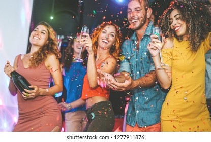 Happy friends doing party drinking champagne and dancing in the club - Millennials young people having fun celebrating in the nightclub - Nightlife, entertainment and festive holidays concept