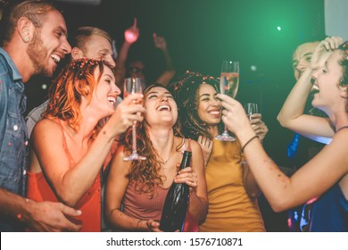 Happy friends doing party drinking champagne in nightclub - Group young people having fun celebrating new year eve holidays together in disco club - Youth culture entertainment lifestyle concept