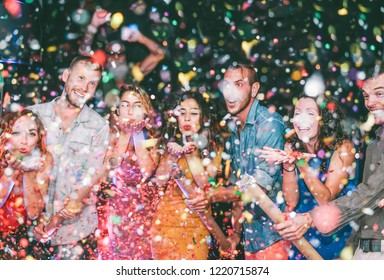 Happy friends doing party throwing confetti in the club - Millennials young people having fun celebrating in the nightclub - Nightlife, entertainment and festive holidays concept