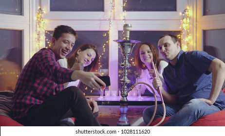 Happy friends doing selfie with mobile phone and smoking hookah in a night bar with beautiful bokeh lights sit by the window