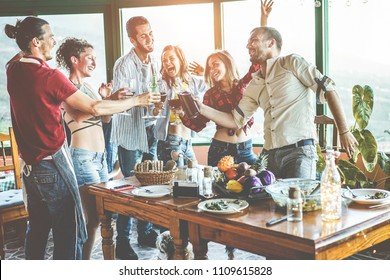 Happy friends doing vegetarian dinner at home - Adult people having fun drinking and eating together - Focus on glasses bottles - Healthy lifestyle and friendship concept