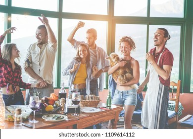 Happy friends doing vegetarian party dinner at home - Adult people having fun drinking and eating together - Focus on glasses bottles - Healthy lifestyle, millennial generation and friendship concept