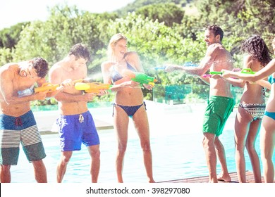 Happy friends doing water gun battle near swimming pool