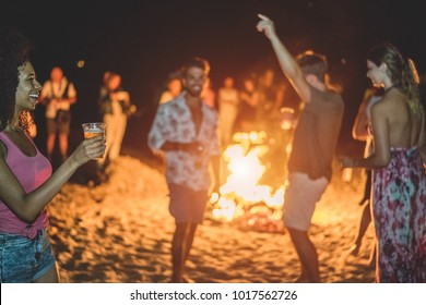 Happy friends drinking beer at beach music festival - Young people having fun summer vacation - Youth lifestyle, holidays and party concept - Soft focus on afro girl hand glass