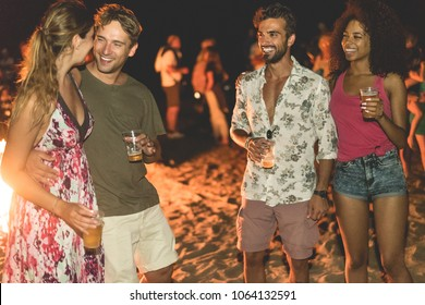 Happy friends drinking beer at beach festival with bonfire in background - Young people having fun summer vacation - Youth lifestyle, holidays and party concept - Main focus on right man