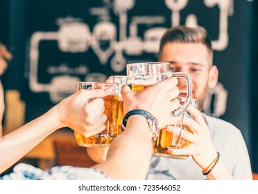 Happy Friends Drinking Beer And Clinking Glasses At Pub, Leisure, Friendship And Celebration Concept. Beautiful Background Of The Oktoberfest. A Group Of Young People While Relaxing At The Bar