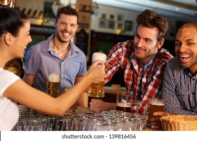 Happy friends drinking beer at counter in pub, chatting with female bartender, smiling.