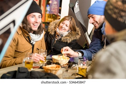 Happy friends drinking beer and eating chips - Cheerful people having fun at bar restaurant after skiing in resort with snow equipment - Friendship concept on warm night filter with focus on woman