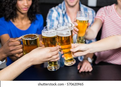 Happy friends drinking beer and toasting in a bar