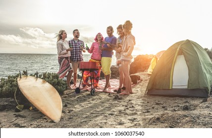 Happy friends drinking beers at camping barbecue picnic next to the ocean - Surfers people having fun and laughing together - Main focus on right guys - Travel, vacation and friendship concept