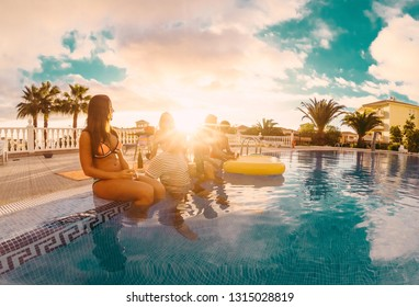 Happy friends drinking champagne in pool party at sunset - Young people having fun in exclusive tropical vacation - Summer holiday, youth lifestyle and friendship concept - Tilted horizon composition