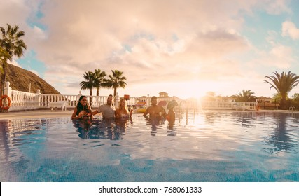 Happy friends drinking champagne in pool party at sunset - Rich people having fun in exclusive tropical vacation - Holiday and friendship concept - Main focus on left guys - Original sun colors tones