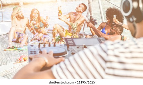 Happy friends drinking champagne in summer boat party - Young millennials people having fun drinking together with dj mixing music - Youth lifestyle and vacation concept - Focus on center man