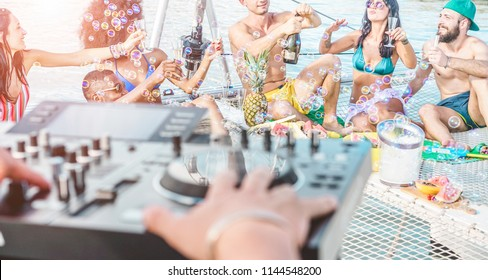 Happy friends drinking champagne in summer boat party - Young millennials people having fun drinking together with dj mixing music - Youth lifestyle and vacation concept - Focus on right guys