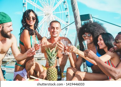 Happy friends drinking champagne in summer boat party - Young people having fun celebrating and cheering - Youth lifestyle, exclusive fest and vacation concept - Main focus on hands glasses