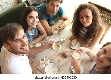 Happy friends drinking coffee in cafe