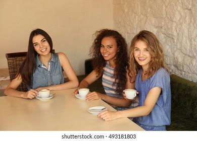 Happy friends drinking coffee in cafe