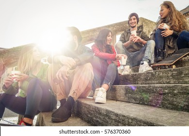 Happy friends drinking paper cup coffee take away on city staircase - Young people having fun outdoor in university break - Friendship concept - Warm filter - Focus on center guys with back light